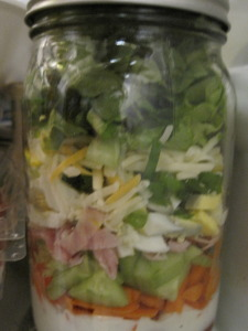 lettuce is added to chef's salad in a jar.