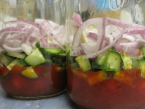 cucumber and red onion added to spinach salad in a jar