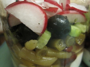 Ripe olives and sliced radishes are added to the jar
