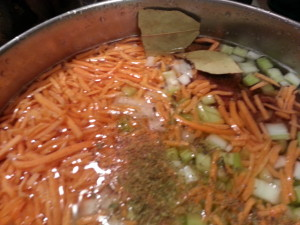 beans, onions, celery, carrots, oregano, and bay leaves are placed in a pot to boil.