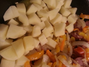 push the peppers and onions to one half of the pan then put in the chopped potatoes