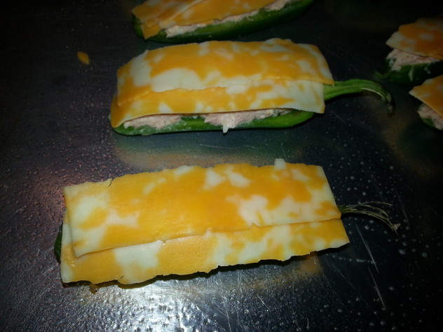 Tuna filled jalapenos topped with strips of cheese before baking