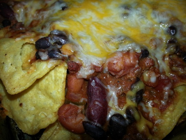 tortilla chips topped with chili and cheese are baked for nachos