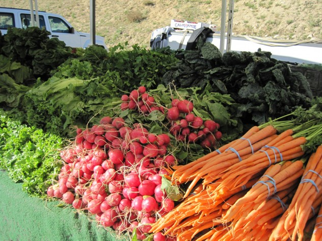A display of carrots, radishes, lettuce and other greens on display at the Farmer's Market