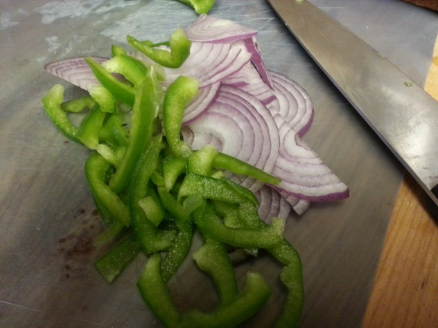 An onion and bell pepper are halved and then thinly sliced.