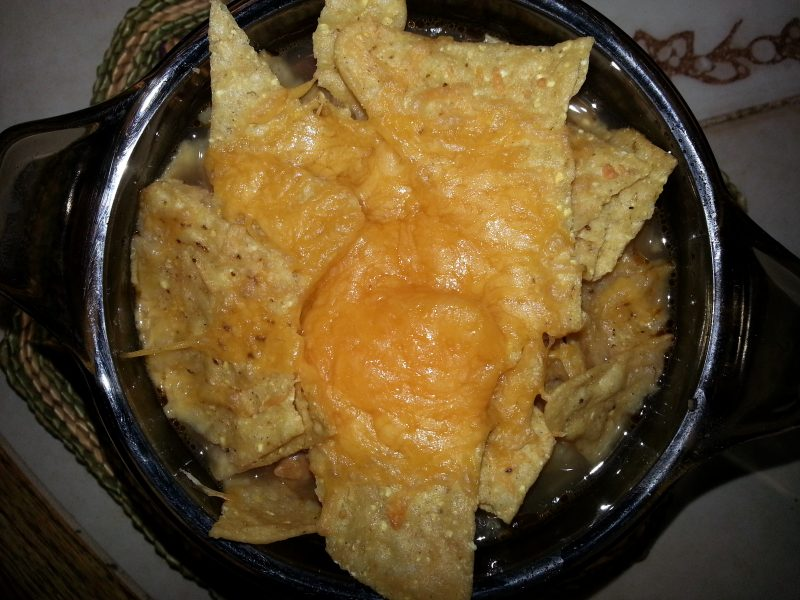 Chicken Tortilla Soup topped with melted cheese and tortill chips top the soup.