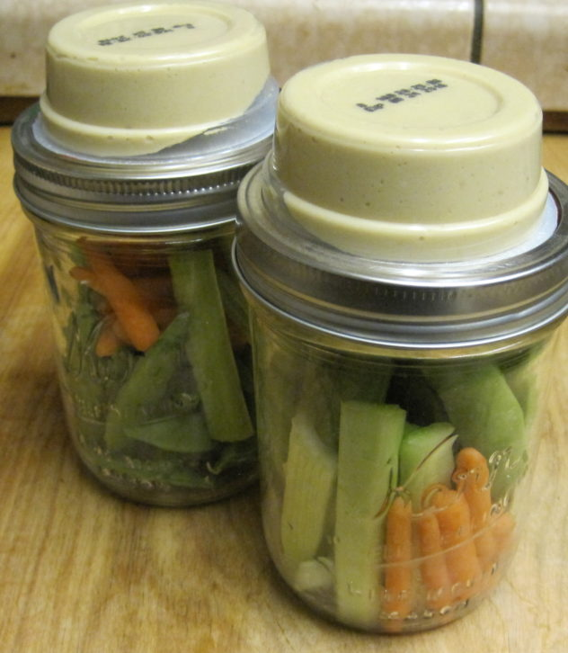 Hummus and Veggie jars--fresh cruciferous vegetables are arranged in a wide mouth mason jar that is topped with a 2 ounce sized serving of hummus. The perfect healthy grab and go lunch.