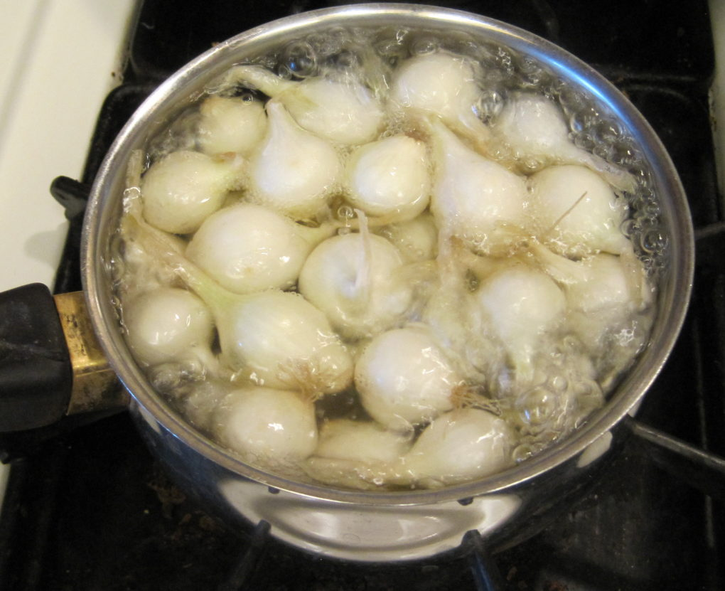 Pearl onions are dropped into a pot of boiling water fior peas and pearl onions