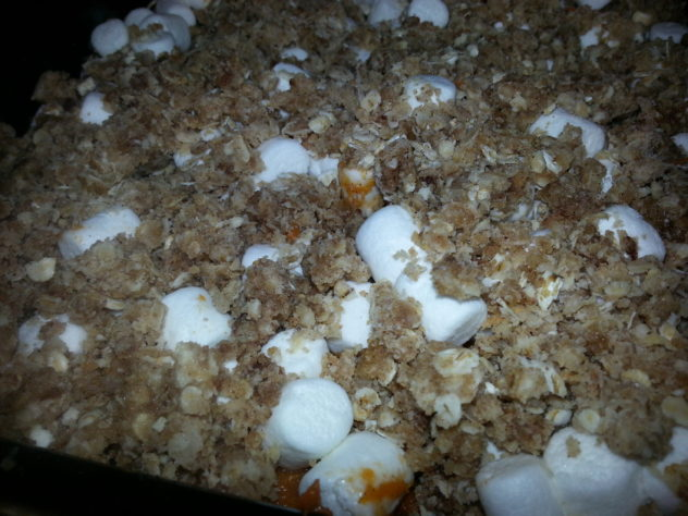 The streusel topping is layered on top of the marshmallows for the sweet potato casserole.
