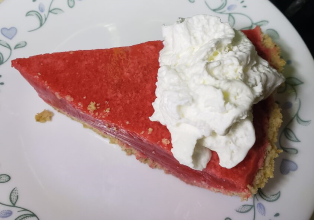 A view of a piece of the raspberry sherbet and geltain pie viewed from above. There is a dollop of whipped cream is on top. The filling is a muted and cloudy magenta.