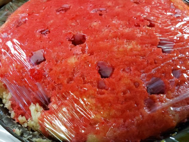 A cake coated in red liquid gelatin is covered with plastic wrap.
