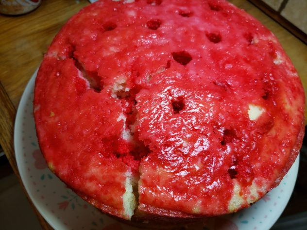 A red colored cake has a large crack in it breaking off nearly  one-fourth of the cake.  It is st with the pieces closely approximated.