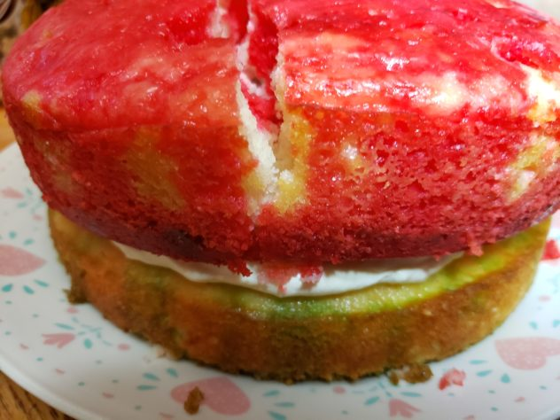 A green layer of cake is under a red layer of cake. White frosting is visible between the layers.