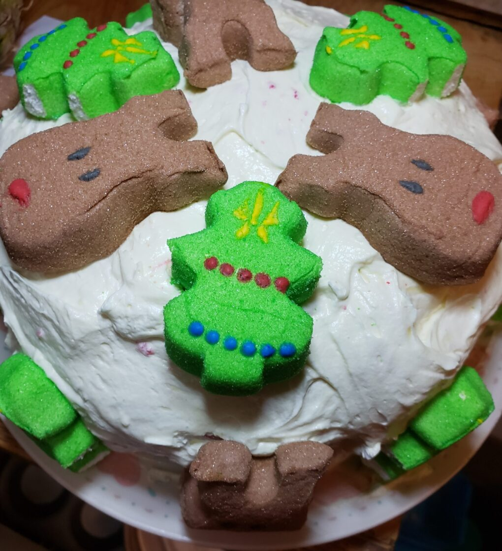 A cake frosted with white frosting is topped with green marshmallow peep christans trees, and brown marshmallow peep reindeer alternated around the top and sides.