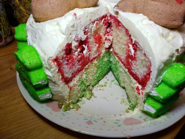 A view of a layered Holiday Poke cake with red streaking the top layer and green streaking the bottom layer. There are marshmallow christmas trees on tierh side of the area where a piece of cake has been removed.