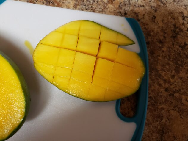 A mango that has flesh that has been cut into squares.  On the top edge of the mango, there is a section of fles that has been cut all the way through the skin which is an error when making mango flowers.