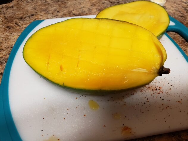 A half of a mango sits in the front of this photo.  Barely visible are the cuts that were made through the flesh in preparation to turn this into a mango flower.
