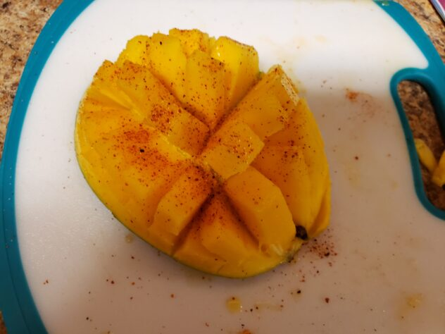 """A picture form the top of a mango that has had the flesh  cut into cubes, but not separated from the skin is visible sitting atop a white cutting board with a bluish trim.  The orange flesh is separated into finger like protrusions as the mang0 has been pushed slightly """"inside out"""" making the skin on the back which is not visible be concave.   This causes the finger-like protrusions to separate creating the """"petals"""" of the mango flower.  The surface has been sprinkled with chili lime seasoning which leaves granules of red powder on top."""