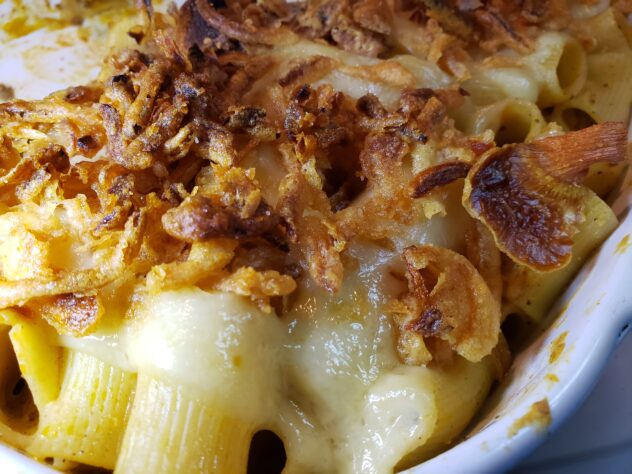 A top view of a corner of the pan of Creamy French Onion Rigatoni. The noodles tinted gold from the sauce are visible beneath a laer of french fried onions that ar a dark golden brown.