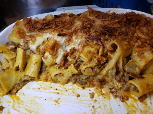 A pan, half eaten of rigatoni tht is colored golden by the mushroom sauce. Visible pieces of cooked ground beef can be seen among the noodles. A layer of browned french fried onions are on top. One side has a slice of melted cheese visible under the french fried onions.