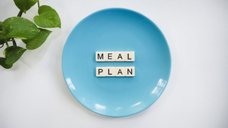 """A blue plate with small letter tiles spelling out """"meal plan."""""""