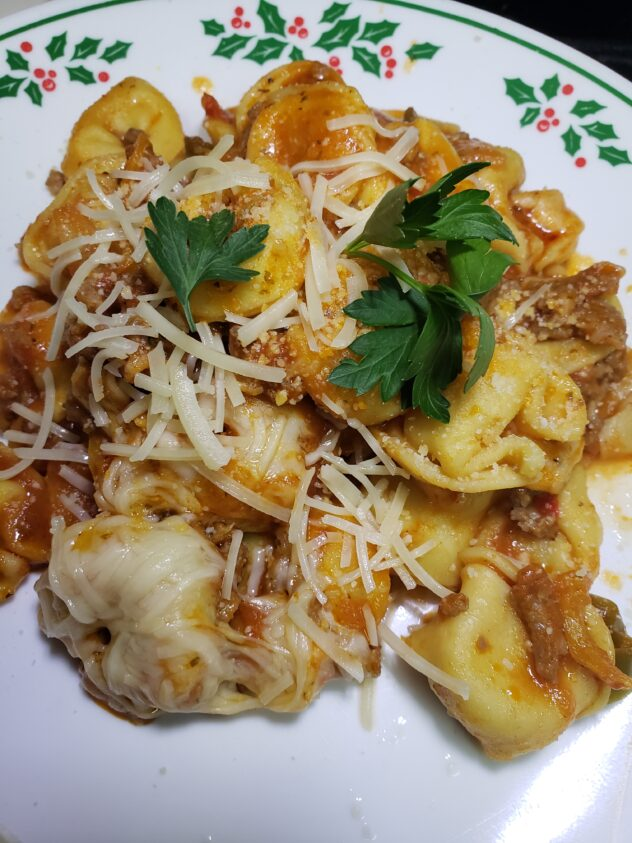 A plated serving of sausage and pepper tortellini sprinkled with parmesan cheese and fresh parsley leaves