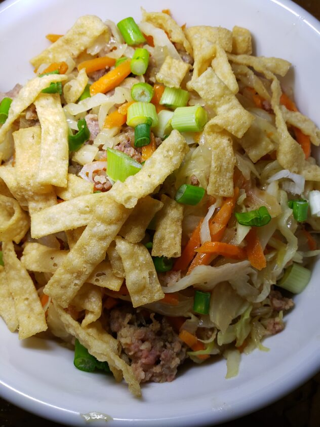 Looking down into a bowl which contains slices of cooked cabbage, bround meat, visibile slices of onion, and julienned carrot. The bowl is topped with sliced green onions and fried wonton strips.