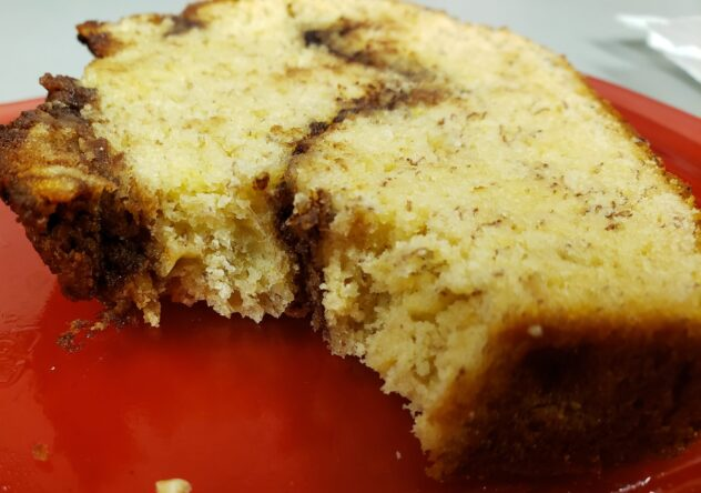 A slice of Nutella Swirl Banana Bread lying on its sideon a red surface. A bite has been taken from one corner. The line oof Nutella is visible running through the slice of bread.