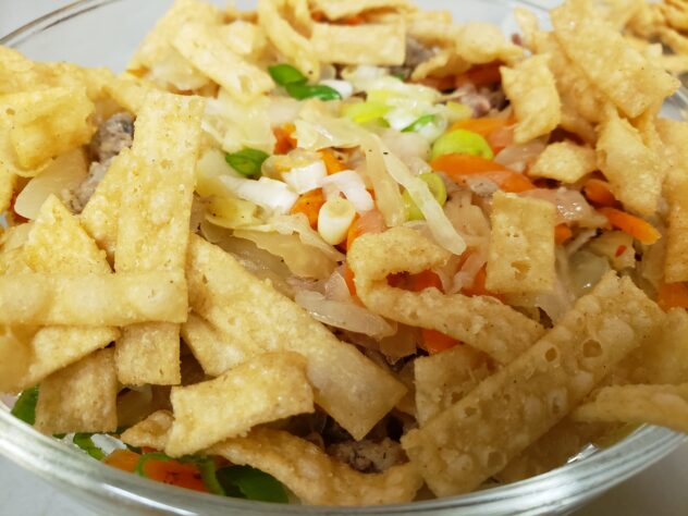 Looking a a bowl full of egg roll in a bowl from the side. The vegetables and meat are barely visible through the layer of friend wonton strops on around the edge and on top. Green onions are visible in the center.