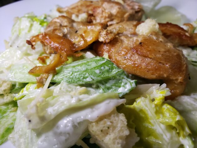 A plated portion of grilled chicken Caesar