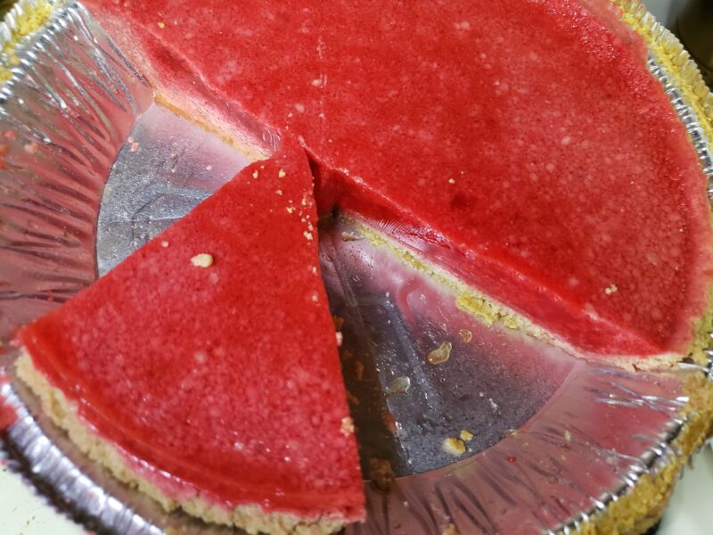 A view of a raspberry sherbet and gelatin pie in a pie plate. The pie is magenta, but the filling is cloudy. Half of the pie is intact, some pieces are missing. One piece if offset from the pie at a 90 degree angle to the intact half.