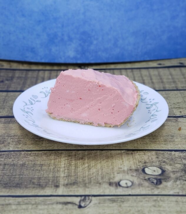 A wedge of tall and fluffy cherry cloud pie is on a white plate sitting on a wood paneled surface. A blue background is behind the piece of pie.