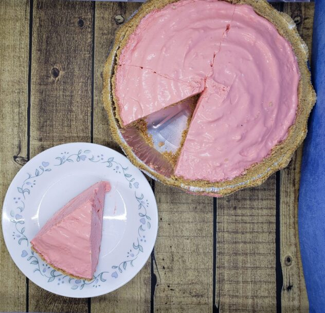 A view looking down on a fluffy pink pie with one piece missing. The missing pices is sitting on a white plate next to the pie.