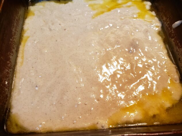 A view of a cream colored batter spread across the bottom of an eight by eight pan with melted butter oozing out from around the edges.