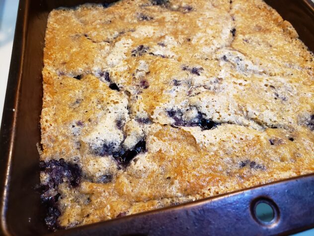 The baked blueberry cobbler is in a pan. The crust is golden brown with some cracks in the surface where the cooked blueberry filling can be seen seeping though these cracks. Where the filling is emerging, there is a stark contrast between the golden crust and the dark purplish filling.