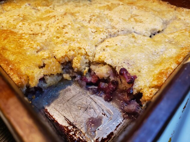The baked Blackberry cobbler has a golden crust. The front corner of the cobbler has been removed to expose the filling with visible blackberries in a gooey filling.