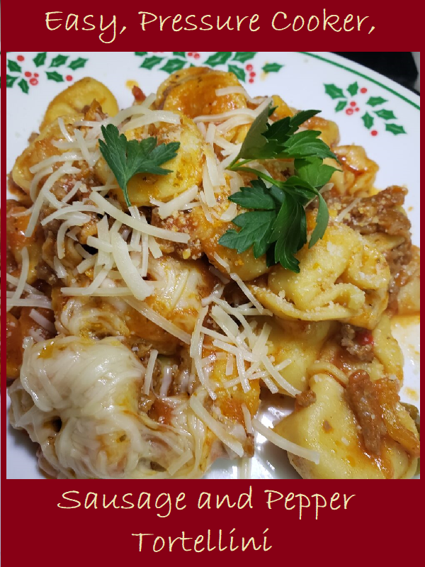 A plated portion of Sausage and Pepper Tortellini with parmesan cheese and parsley sprinkled on top.