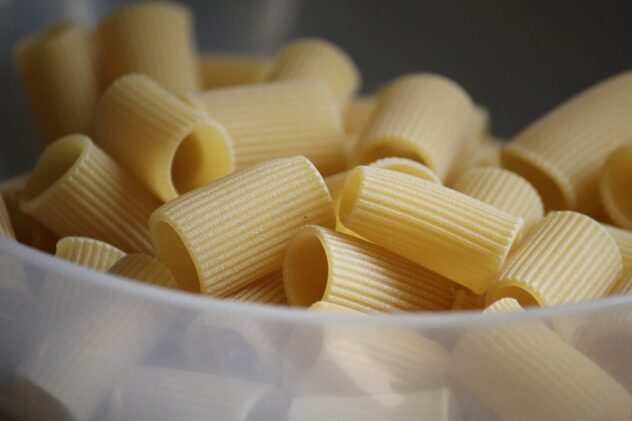 A bowl filled with uncooked rigatoni noodles
