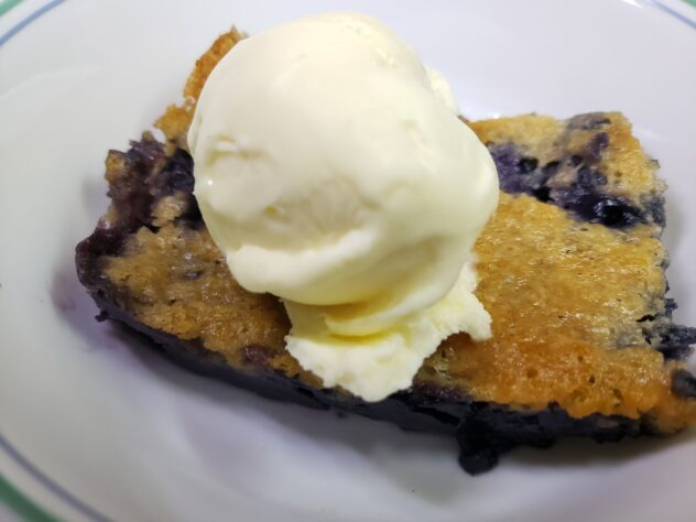 A scoop of vanilla ice cream sits atop a piece of blueberry cobbler. The ice cream is creamy white and melting slightly as it sits atop the golden crust of the cobbler. Cracks in the crust show small areas with blueberries seeping through. Underneath, the gooey blueberry filling is visible spreading slightly out from the base of the piece of cobbler. The cobbler is sitting in a white bowl.
