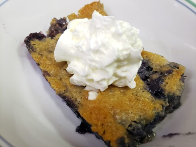 A piece of cobbler with the dark, gooey filling visible underneath topped with a dollop of whipped cream.