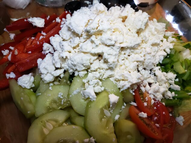 A circular arrangement of cucumber slices, halved red cherry tomatoes, thin strips of red bell pepper, halved black olives, sliced green onions and a pile of crumbled ricotta cheese in the center.