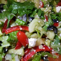 A view into a bowl containing a tossed salad. Visible in the bowl is an array of vegetables including lettuce, half cherry tomatoes, halved large blace olives, red bell pepper, and cucumber slices tossed with pieces of crumbled feta cheese. The vegetables are glistening due to being tossed with dressing.