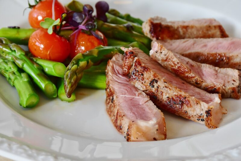 A plate filled with slices of rare meat with beautiful carmelization around the edges, asparagus, and tomatoes.