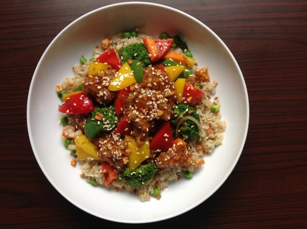 A large white bowl with a layer of brown rice, topped with broccoli beef and red and yellow peppers.  It's all tossed in a thick brown sauce and sprinkled with sesame seeds.