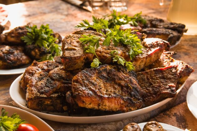 A platter loaded with beautifully carmelized steaks that is topped with fresh parsley.