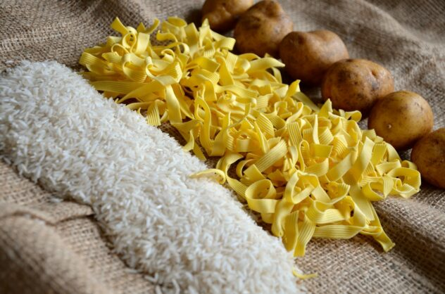 A sheet of clean burlap is topped with a row of uncooked rice, a row of dried noodles, and a row of raw potatoes.
