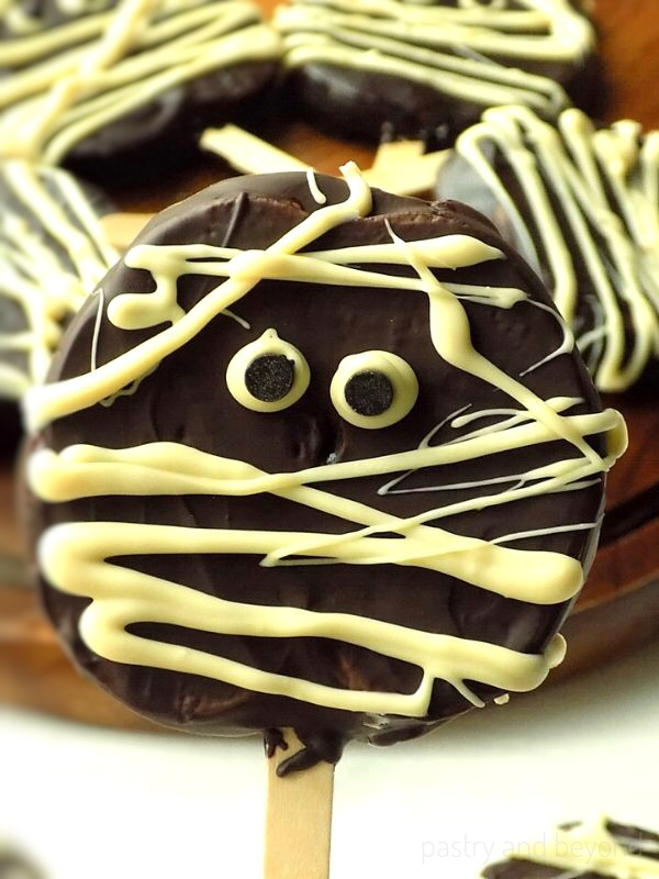 This fruit based Halloween treat is a disk of sliced apple that's been dipped in chocolate and decorated with a cream colored frosting to mimic the wrappings on a mummy.  Frosting eyes peek between the lines.
