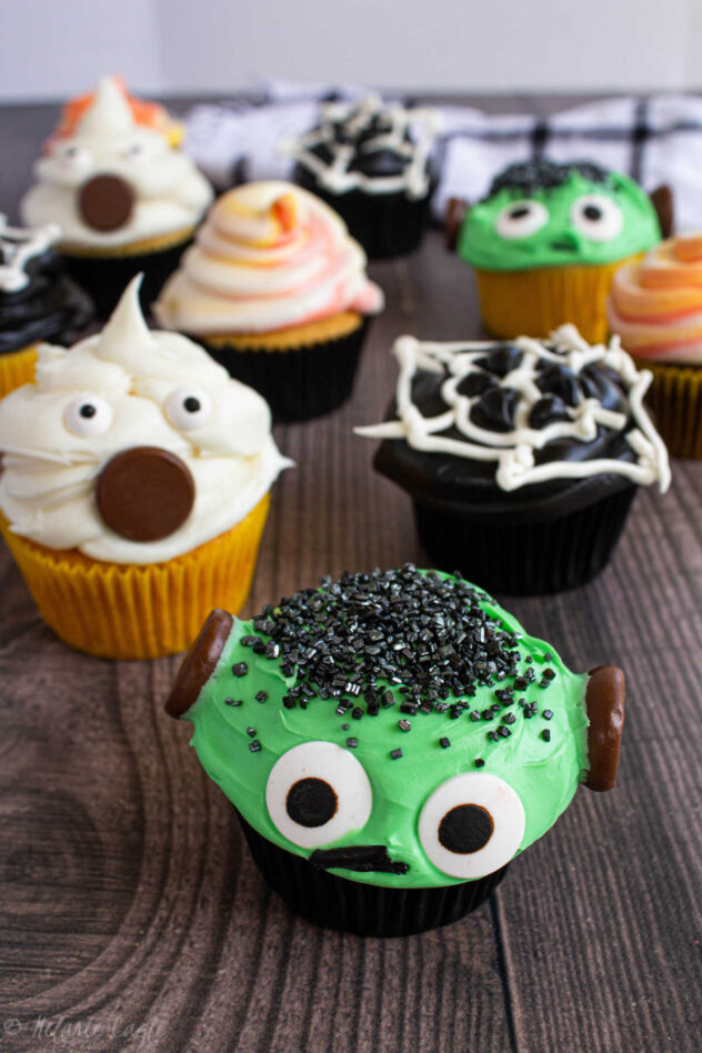 This is a collection of Halloween themed cupcakes with instructions for decorating them.  There are ghosts, Frankenstein's monster cupcakes, cupcakes topped with white chocolate spiderwebs, and some frosted with mixed color frosting (orange-yellow, white).