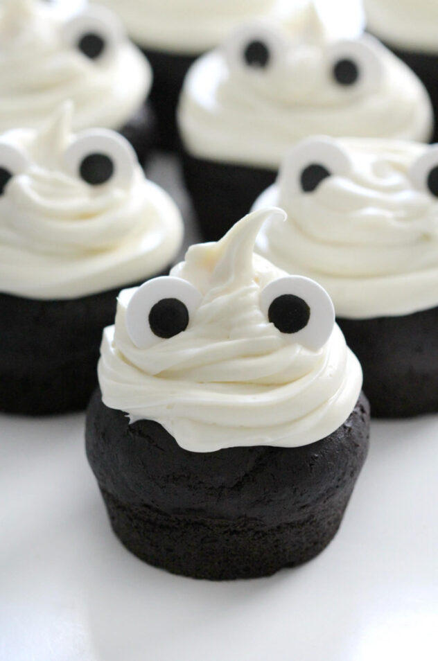These vegan and gluten free Halloween themed cupcakes are chocolate cupcakes frosted with a white frosting.  The cupcakes are each topped with two edible eye candies to create the appearance of a ghost.
