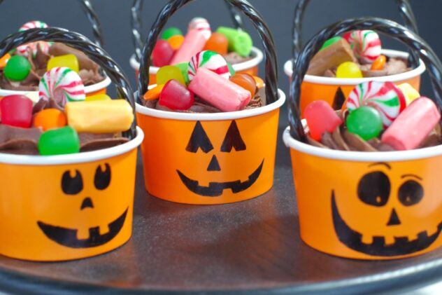 Paper jack-o-lantern cups are fulled with a chocolate cupcake that is topped with candy.  A handle made from a black twisted licorice strand is positioned as a handle on these Halloween themed cupcakes.